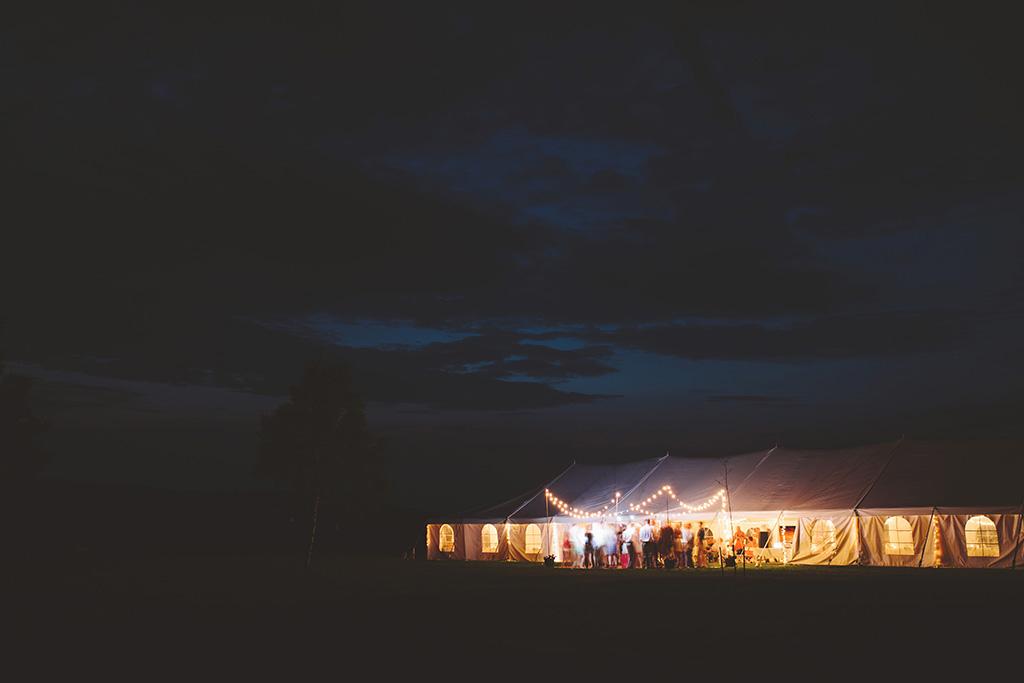 Glowing magical wedding reception tent under night sky