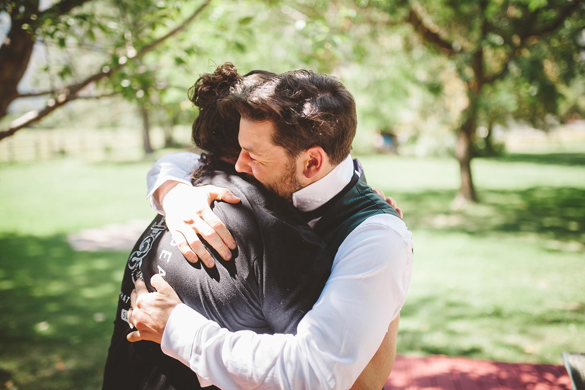groom hugs before mountain wedding