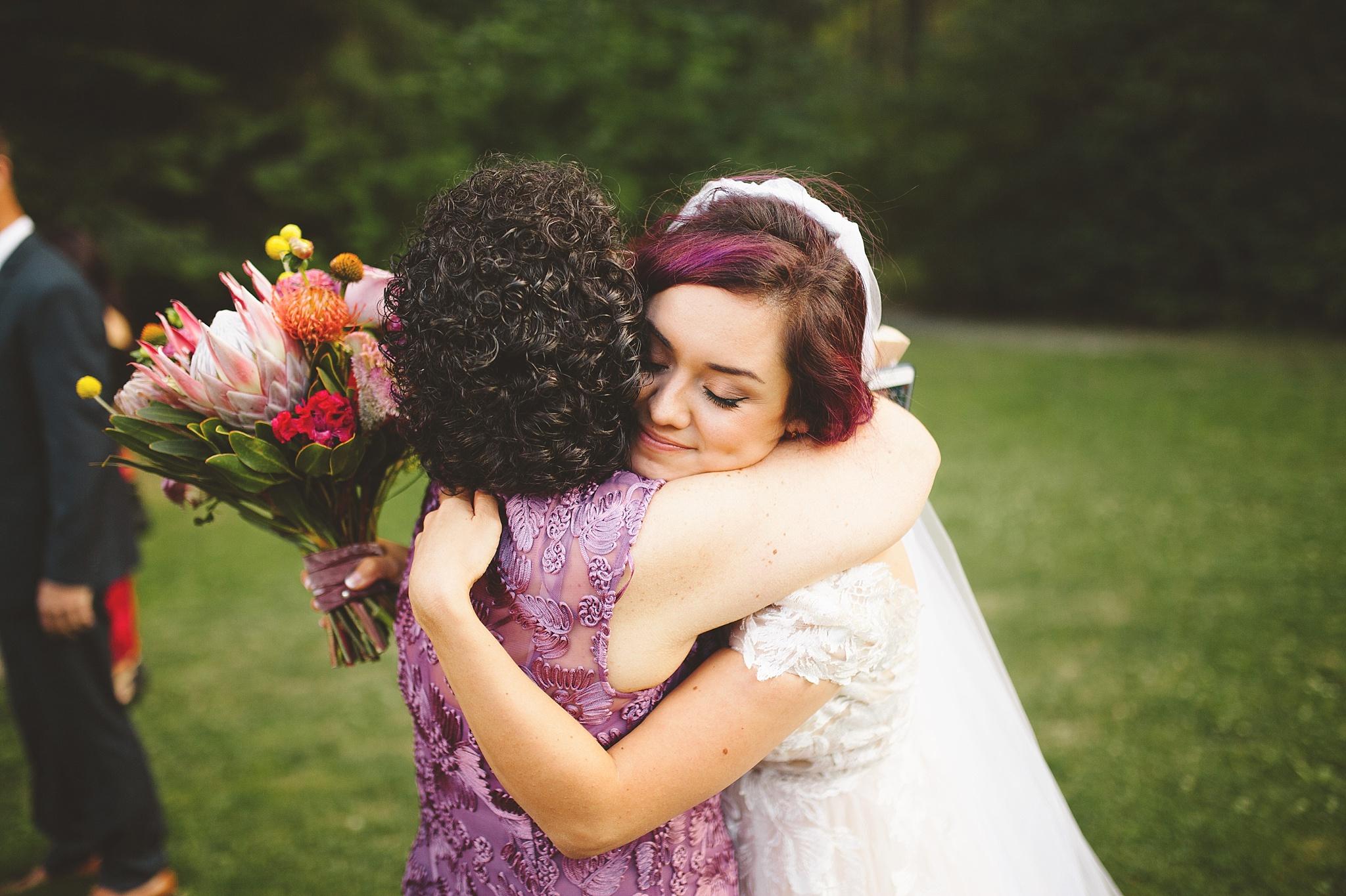 mom hugs bride after wedding