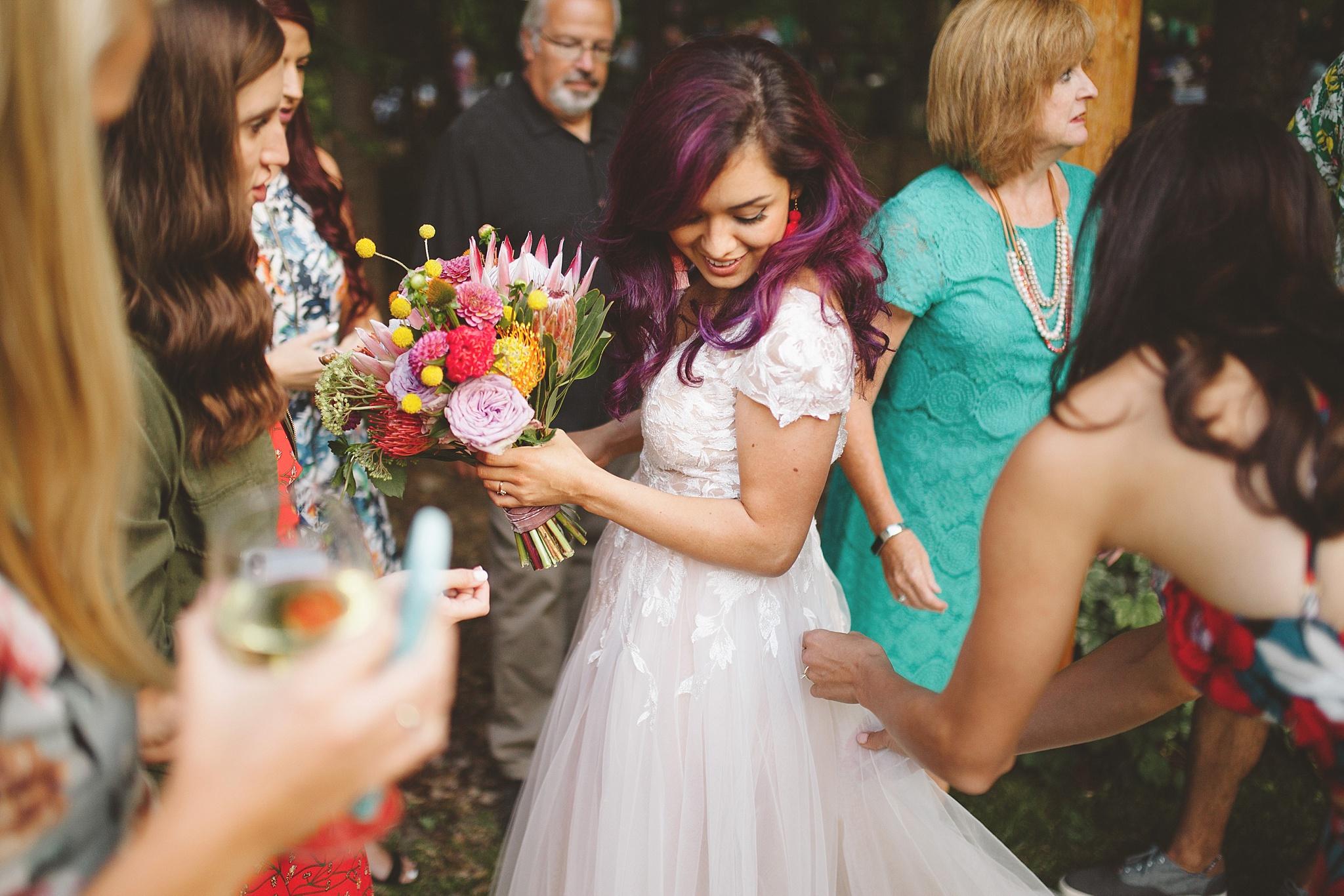 bride fixes her dress at mountain wedding PNW