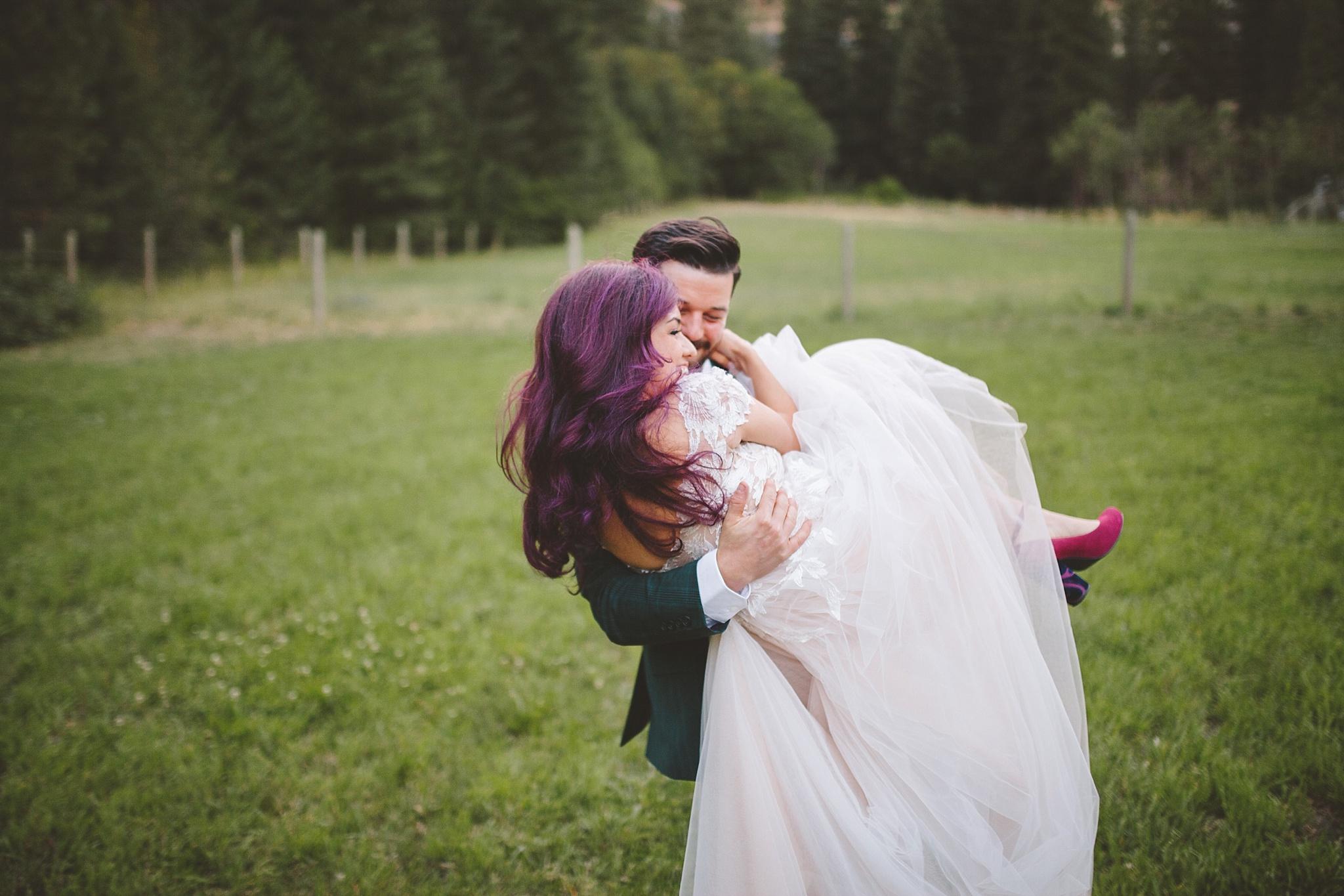 groom carries bride through the woods on wedding