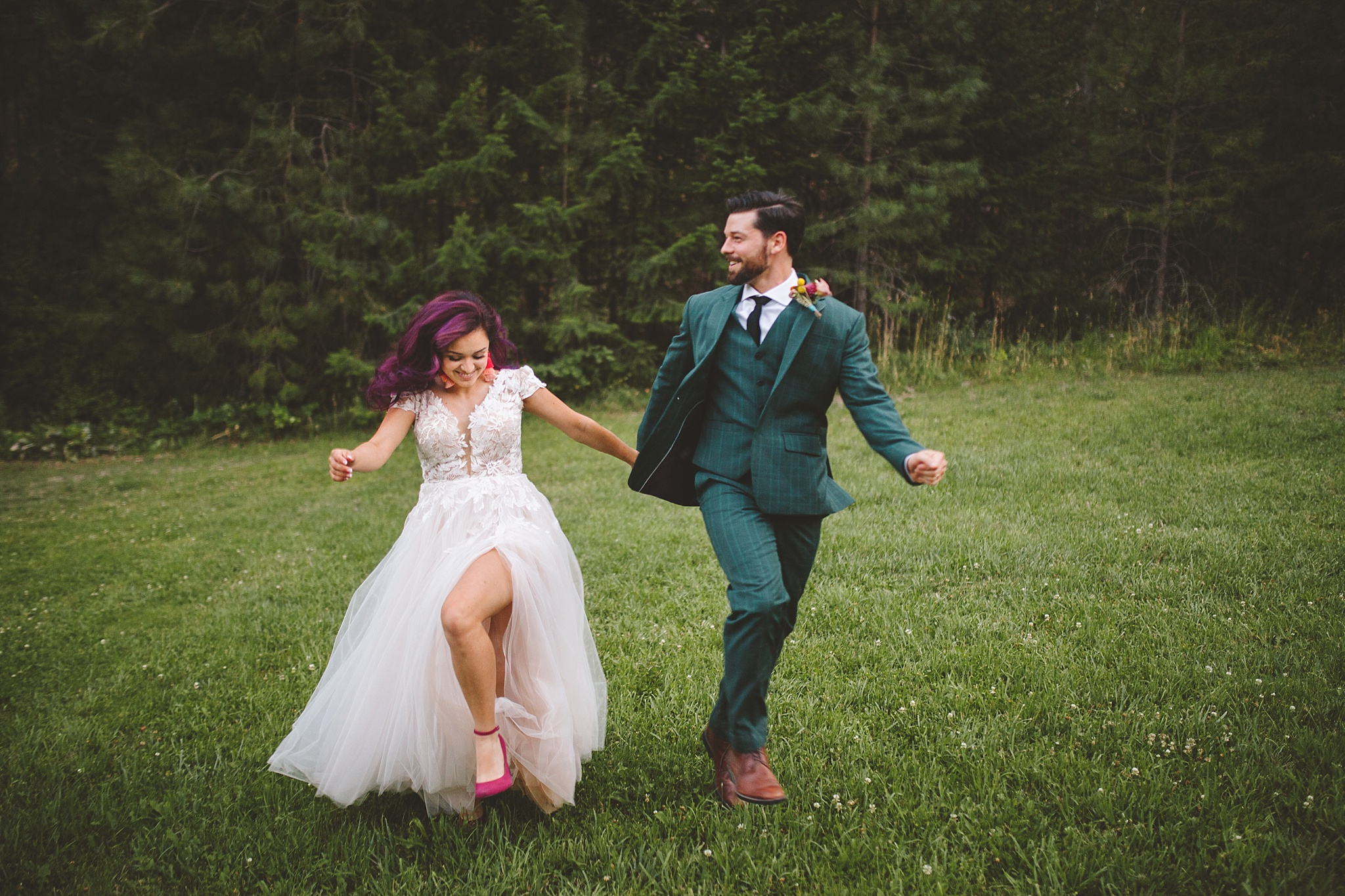 bride and groom run through the woods
